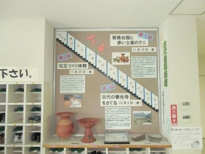 赤い土器や瓦の実物、文章パネルが展示されている画像