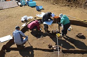 竪穴住居から出土した土器の図面を描いている様子