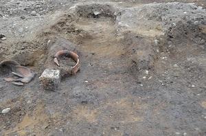 竪穴住居跡から見つかったカマドの跡の写真です。使われていた土器やカマドの石が残されています。