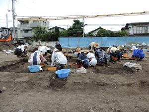 作業員さんが竪穴住居跡を掘っている写真です。