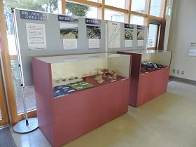 展示ケースに入った出土品と遺跡の解説パネル