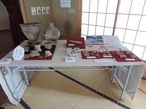 左側に昭和の調査で見つかった新諏訪町式土器土器。右側に平成の調査で見つかった土器や石器、金属製品などを展示した様子