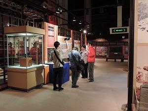 取材の様子の写真です。展示ケースの前で4人の人が説明をしたりカメラで撮影したりしています。
