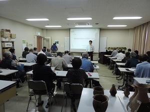 職員がスライドの解説をして、それを見ている受講生の方々の様子