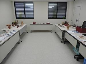 コの字に並んだテーブルの上に弥生時代~古墳時代の遺物や現場で撮った写真パネルが展示してある様子。