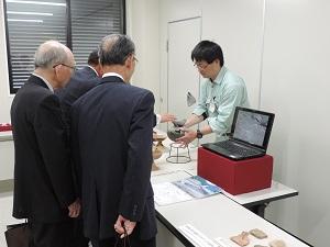 職員が見学者3人に古墳時代の土器の説明をしている写真