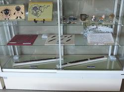 展示ケースを正面からみたところ。一番下の段に大刀と剣、その上の段に鏃と臼玉を展示している様子