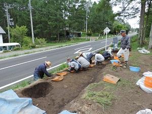 10人程の作業員が、小さいスコップを使って土を掘っています。