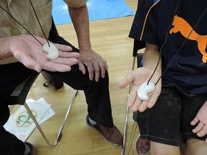 2人の参加者が、完成した勾玉に紐を付け、首にかけて手にのせ見せている様子