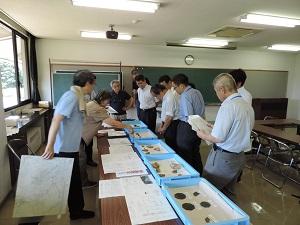 出土品を入れた箱が机の上にいくつも並べられています。机の左には出土品の説明をする長野市の職員がいます。机の右にはそれを聞く8人の出席者がいます。