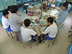 4名の生徒が椅子に座って職員から拓本の説明を受けている様子