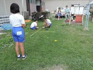 2名の生徒が図面を書き、2名の生徒が機械を使って遺物の高さを測っている様子です