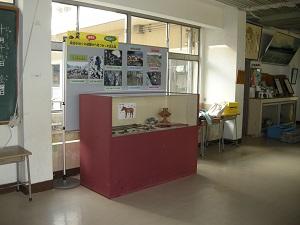 パーテーションに貼られた発掘調査の写真と展示ケースに入った鉄製品や土器などの遺物