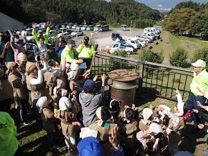 カレーを煮込む大釜のまわりに、古代衣装を着た子供がたくさんいます。大釜に火が入り、みんなで万歳をしています。