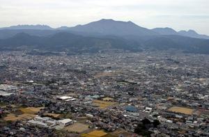 長野市南東からの空撮写真です。中央には長野市街地、奥には飯縄山が写っています。