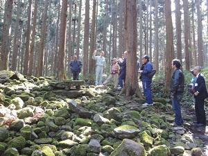 古墳のまわりで説明を受ける6名の見学者を撮影した写真