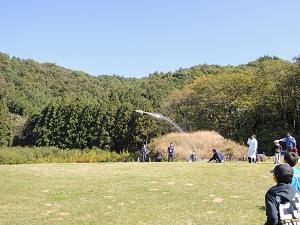 ゆるやかな坂の上にある古墳から、下の芝生に向かってロケットが飛んでいます。ロケットからは燃料の水が吹き出しています。