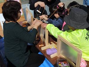 指導を受けながら子供がたわら編みをしているようす。角棒を四角く組み合わせた枠を使い、木の棒を赤い糸で編み込んでいます。