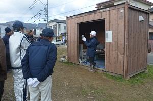 左側の見学者に職員が土器を持ちながら説明している写真です。