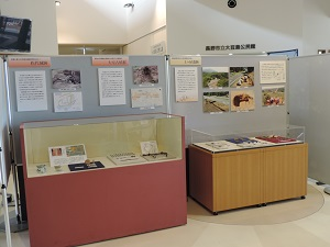 2台の展示ケースに陶磁器や鉄製品、石器などが並んでいる様子。ケースの後ろにはパネル展示がしてあります。