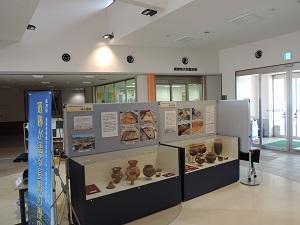 2台の展示ケースに土器や石器などが並んでいる様子。ケースの後ろには写真パネルの展示がしてあります。