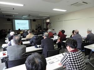 部屋の奥に講師が立ち、スライドの前で講演しています。手前には椅子に座るたくさんの聴講者がいます。