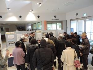 展示品の解説をする講師をたくさんの聴講者が取り囲んでいます