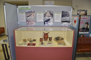発掘調査の写真パネルと、展示ケースに入った土器や埴輪が写っています。