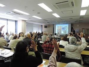 部屋の奥に講師が立ち、スライドの前で講演しています。手前には椅子に座るたくさんの聴講者がおり、挙手をしています。