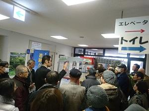 展示品の解説をする講師をたくさんの聴講者が取り囲んでいます。