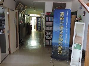 公民館の玄関ホールとそれに続く廊下の写真です。ホールと会場入り口にはバナーが置かれています。