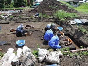 中学生2名と作業員2名がスコップで土を掘っている様子。
