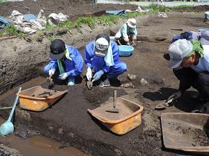 中学生2名が遺構を掘っているようす。スコップで少しずつ土を掘っています。