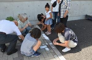 参加者が石を勾玉の形に削っている様子