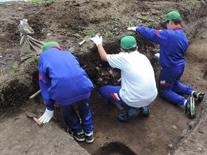 3名の中学生が両刃鎌を使って調査区の壁を削っている様子。