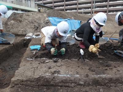 末吉くんが腹ばいになって竪穴住居跡を掘っているようす