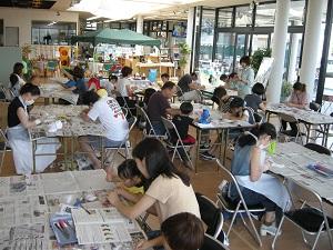 4人から5人掛けの机が約8台並び、参加者がグループごとに席についている様子。