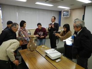 展示した土器の解説をする発表者とそれを聞く聴講者の写真