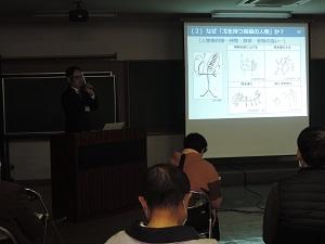 講師が聴講者に講演をしています。