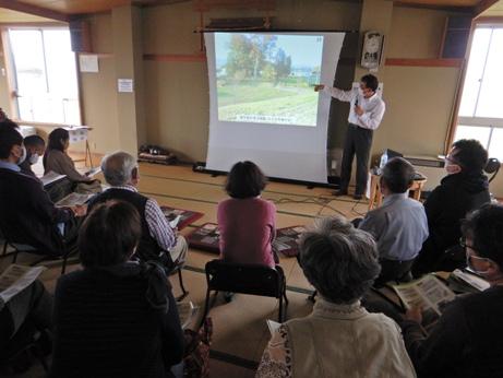 報告会で講師がスクリーンに映し出された写真を説明しているようす