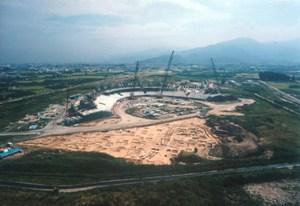 南宮遺跡の空撮写真です。手前には発掘された遺跡があり、奥ではオリンピックスタジアムの建設が行われている写真です。