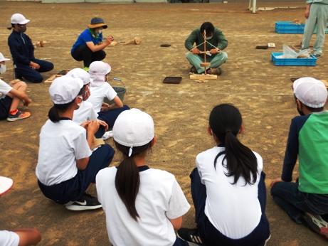グラウンドで火おこしのデモンストレーションに見入る吉田小6年生