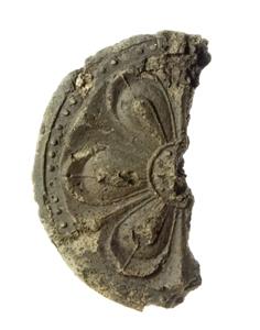 元善町遺跡から出土した軒丸瓦の文様面の写真です。破片で半分だけ残っています。
