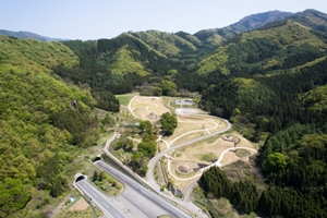 史跡大室古墳群の空撮写真です。手前に上信越自動車道、中央にエントランスゾーンの古墳群が写っていて、上部には大室古墳館が見えます。