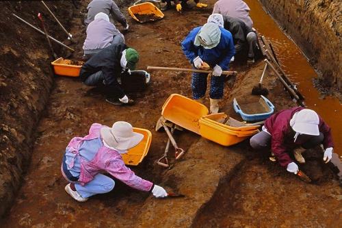 発掘作業員がスコップなどの道具を使って遺構の中に埋まった土を掘っている様子