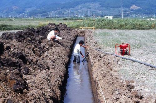 膝丈まで水がたまった調査区の中で調査員が堆積した土の厚みを計測しています。調査区の上では別の調査員がその数値を方眼紙に記録しています。